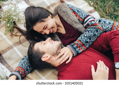 Guy and girl on picnic laugh