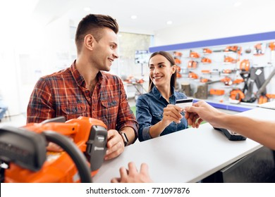The guy and the girl pay for the purchase of a chainsaw. They are in the shops of tools for gardening. They use a credit card.