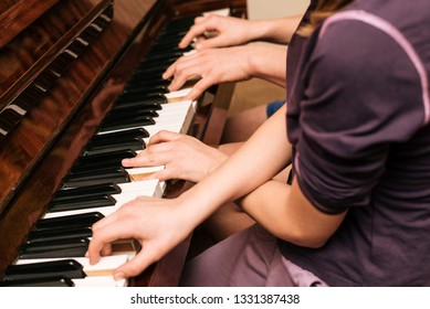 The guy and the girl play the piano in four hands. Brother and sister are studying a new musical composition and playing the piano