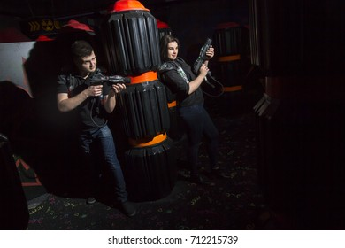 A guy and a girl are playing laser pistols in a dark room