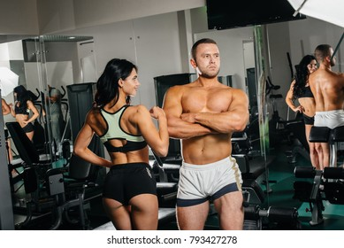 A guy and a girl are posing in the gym. Sport. Fitness.