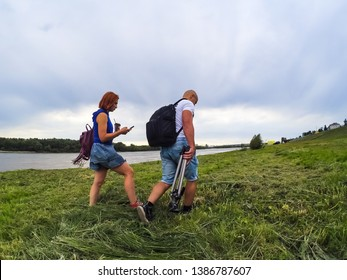 The guy and the girl in shorts and T-shirts go on high green grass on the river bank with backpacks. A woman has coffee and a telephone in her hands, a man has a tripod for a camera. Walk and sports.
