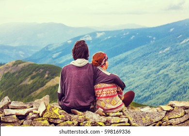 The guy with the girl sit embracing high in the mountains.  Love, friendship, intimacy, enjoy being together.