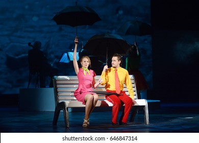 Guy with a girl sit under the umbrellas on a bench