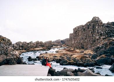 A guy and a girl are sitting embracing on a bridge near Ehsaraurfoss Waterfall, Ehsarau River, National Park, Thingvedlir, the region of Sudurland, Iceland.