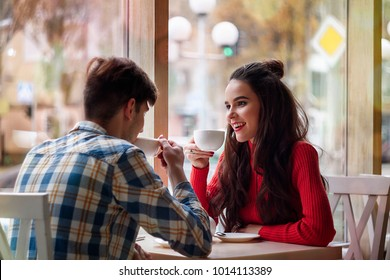 A guy and a girl are sitting together in a cafe. They drink tea. They are in love with each other. They are a couple.