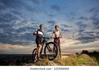 Guy and the girl of a sports constitution stand with bicycles on a stone under a beautiful cloudy evening sky in the background is a city. Bottom photo