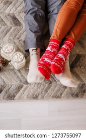 Guy and girl in sweaters sit on the floor in front of the window next to the Christmas tree. Mugs and cones. Feet in red and beige socks. New year 2021