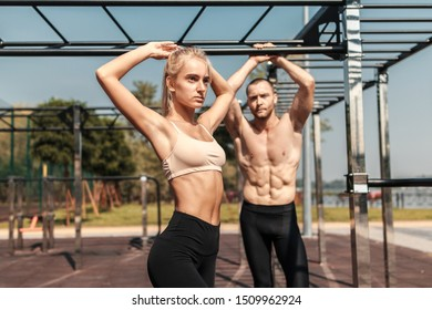 A guy and a girl are training together on the sports ground. Joint training under the sun on the outdoor