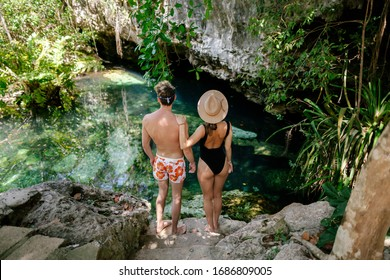 Guy and girl travel in Mexico and visit cenotes on the Yucatan peninsula. Sacred places of the Mayans. Unknown Mexico. Guy and girl in the jungle.