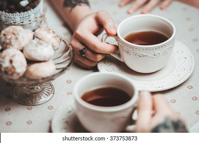 a guy and a girl with two cups of tea at a beautiful table with gingerbread