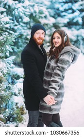 Guy and girl walk and have fun in the forest in winter