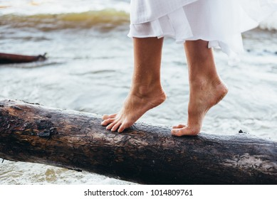a guy and a girl walk on the beach barefoot, the girl rolls the waves and pours it with water splashes, the girl walks on a log lying on the beach neatly stepping barefoot