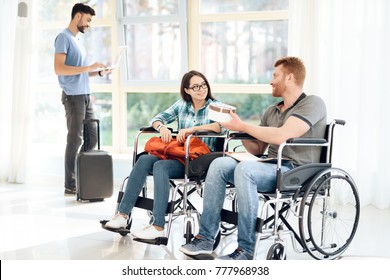 A guy with a girl in a wheelchair is traveling. A paralyzed girl in the airport waiting room. The guy gives the girl in a wheelchair a gift. A paralyzed beautiful girl and lover.