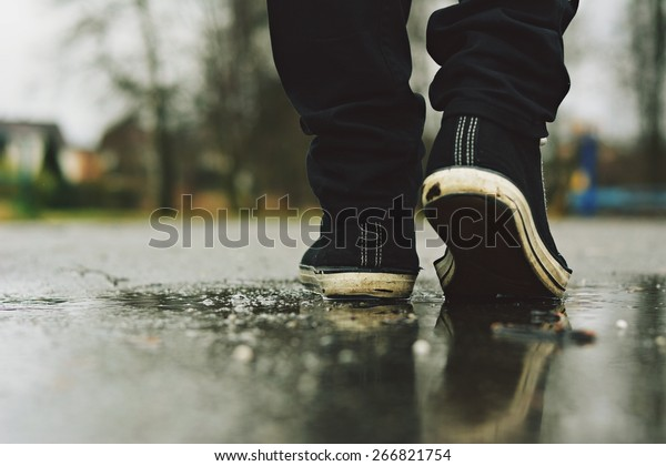 Guy goes in sneakers on the street in the rain