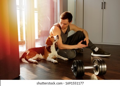 The guy goes in for sports at home with a dog. Exercises for a healthy lifestyle