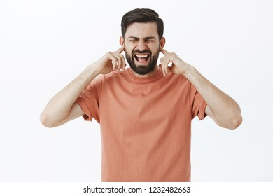 Guy going crazy, losing temper, feeling distressed and uneasy close eyes with index fingers, shut eyes and scream out loud freaked out and displeased, standing bothered of loud noise and crowded place
