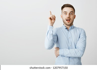 Guy got excellent idea sharing with team. Enthusiastic excited good-looking male in formal blue shirt raising index finger in eureka gesture holding breath and opening mouth while adding suggestion