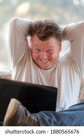 A guy with a grimace holding a laptop on lap with arms overhead. The concept image shows frustration and anger.  He looks like Jack Nicholson from The Shining movie.