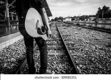 Guy with guitar on the railway road. Black and white photo