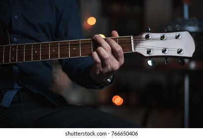 The guy the guitarist plays on a beautiful acoustic guitar in a bar in the evening