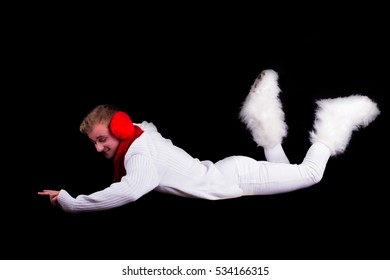 Guy gymnast dressed as christmas elf flying without visible ropes isolated on black background