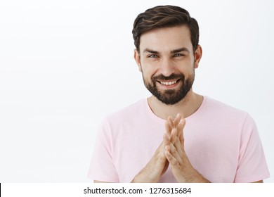 Guy have excellent plan will show how business makes. Handsome smart and creative intelligent caucasian male with beard rubbing palms and smiling delighted having perfect idea over gray wall