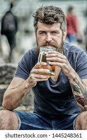 Guy having rest with cold draught beer. Hipster relaxed drinking beer outdoor. Light ales or dark stouts drink them all. Man with beard and mustache hold beer glass outdoors. Cafe summer terrace.