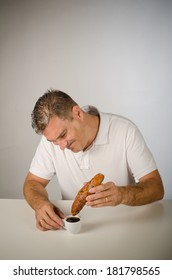 Guy having trouble to dunk his breakfast roll