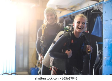 Guy helping a girl dressing up with scuba diver's equipment