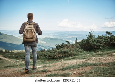 Guy hiking in mountains with rucksack. He standing with focus on back on peak and observing scenery downhill
