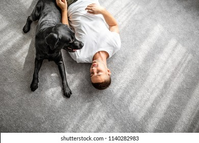 guy with his dog sitting at home playing