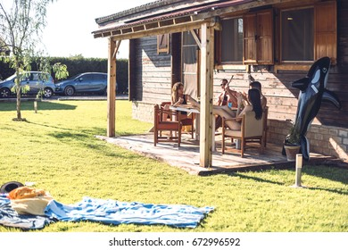 Guy with his friends playing guitar on porch of summerhouse on sunny day.