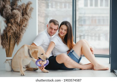 Guy and his girlfriend are resting in bedroom. Happy couple lovingly looking at their pet who wants to play