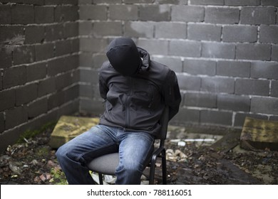 Guy with his hands tied behind his back sits in a chair in abandoned place.