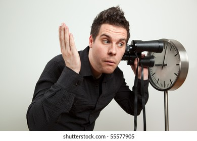 Guy holding binoculars and listening the clock