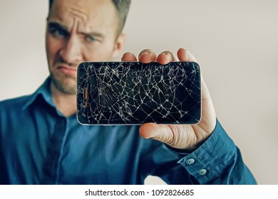 The guy is holding a black smartphone with a broken display. Broken screen of modern frameless phone. a large crack in the form of a web on the smartphone screen close-up.