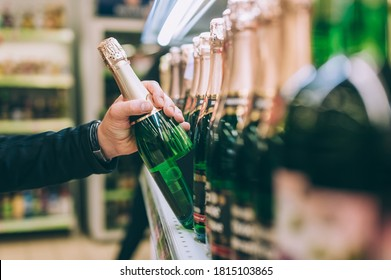 The guy is holding a bottle of champagne in the store
