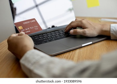 A guy is holding a credit card and filling out his laptop with credit card information, he is shopping online on the web and paying by credit card. Online shopping ideas.