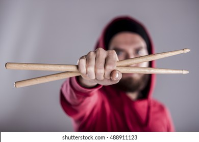The guy holding the drumsticks in his hand.Young man with drumsticks.A bearded man holding a stick in his hands