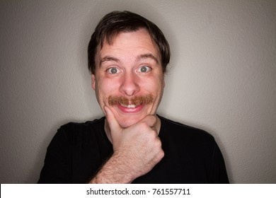 guy holding his chin with a big grin on his face