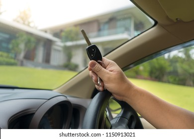 The guy holding the keys in the car parked in front of the new house