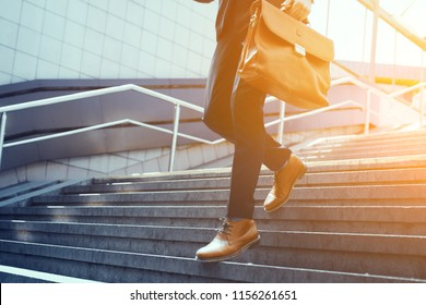 Guy holding leather bag walking down stairs. Businessman wearing suit and brown leather shoes walking down concrete steps. Business concept for office workers and corporate stuff.