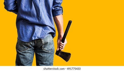 A guy holding old rusty axe, close up rear view, on yellow background with copy space