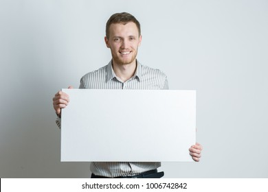 guy holding a white sheet in hands, an office worker showing a blank sheet