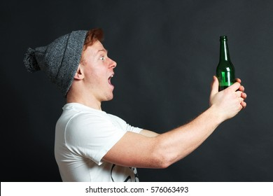 The guy holds beer bottle in hands and is pleased on black background