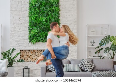 The guy holds the girl on his hands and kisses her / copy space