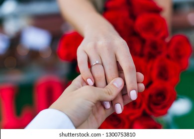 The guy holds the girl's hand on her ring finger a golden ring. Bouquet of red roses in the background