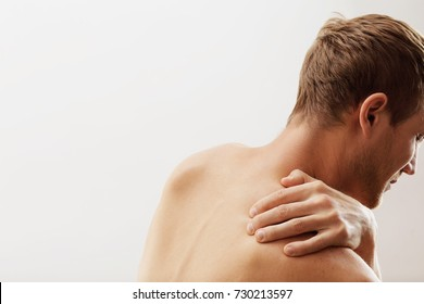 guy holds on to his back, his shoulder hurts