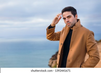 the guy holds one arm at the head and the other hand in his pocket in a beige coat stands on the shore of the ocean